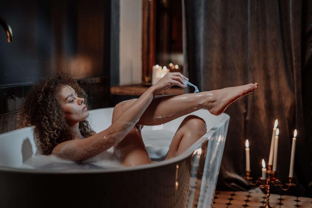 frau rasiert beine in badewanne-erdbeerhaut